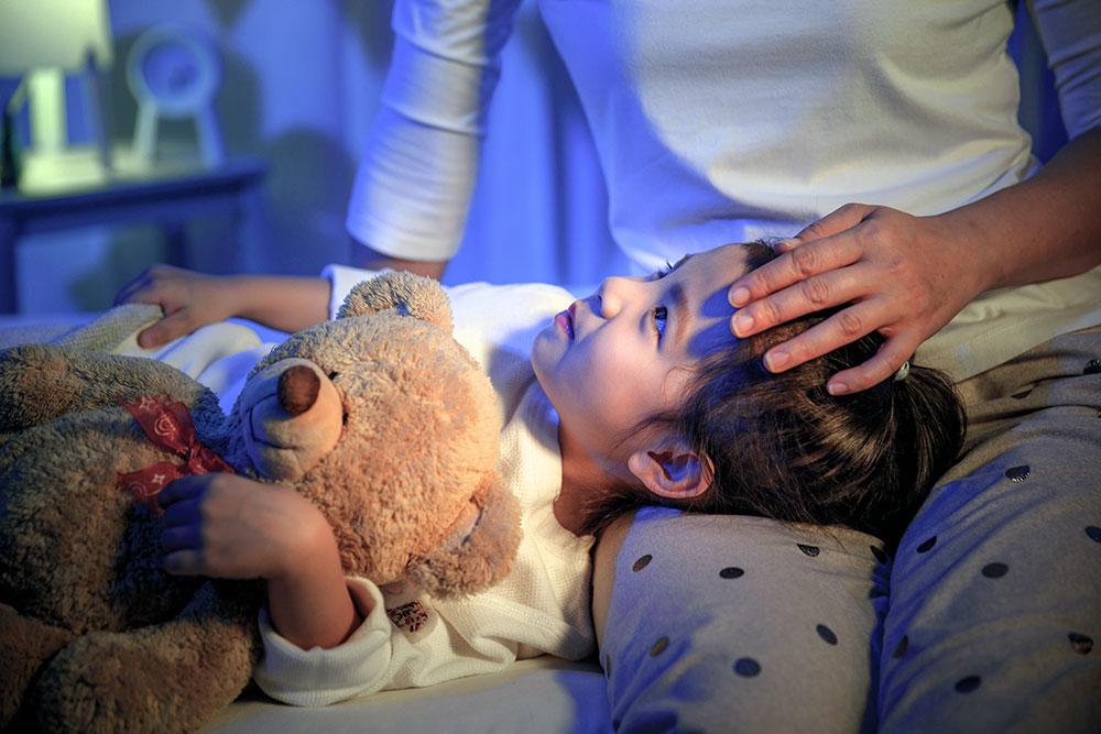 boy on a bed holding teddy bear